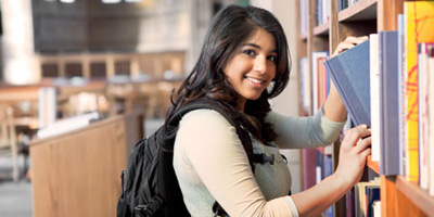 Student browsing through books at academic library