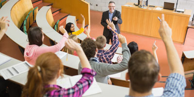 Postsecondary students raising their hands in lecture hall